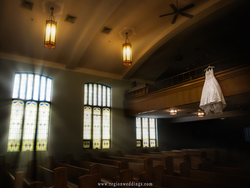 The bride's wedding dress hangs from the balcony at Lowell Methodist Church.