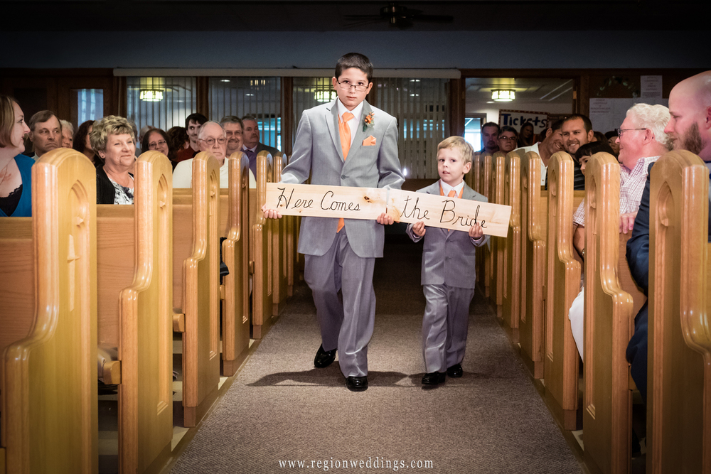 Ring bearers hold up a Here Comes The Bride sign.