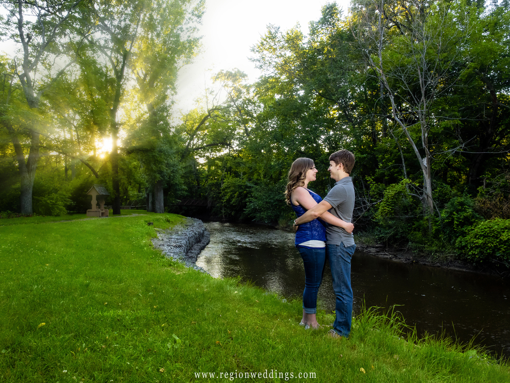 The sun shines through the trees as a young couple embraces along the river.