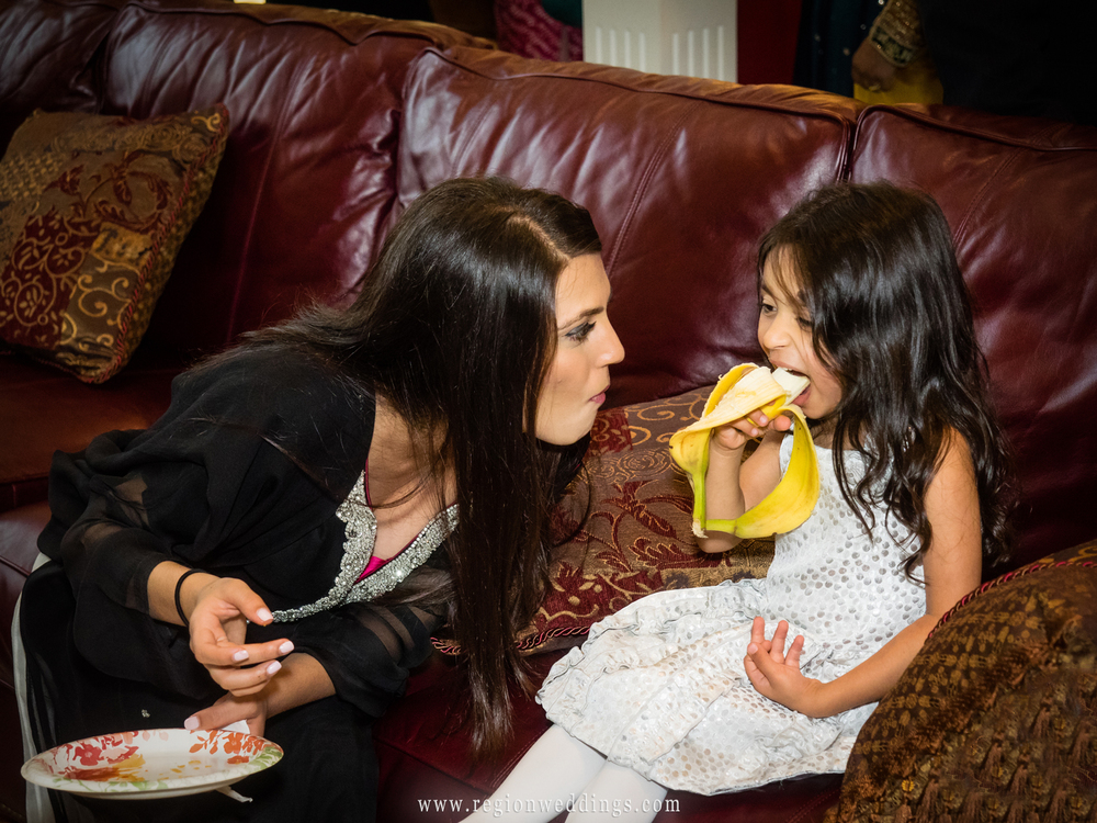 A mom playfully encourages her child to eat a delicious banana at an engagement party in Northwest Indiana.