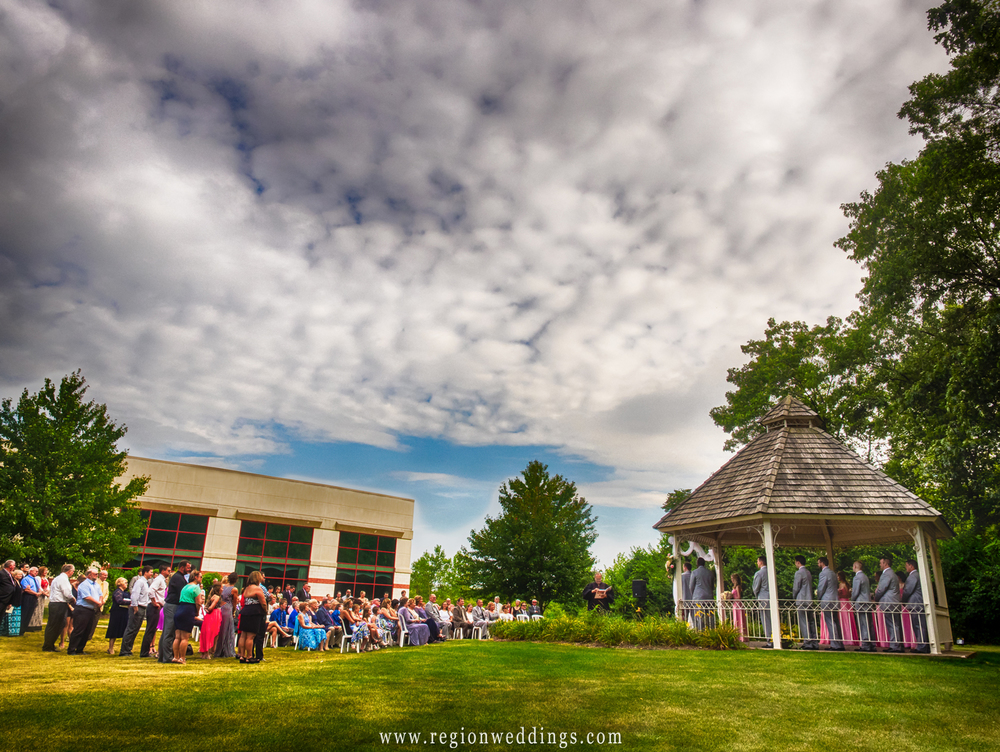 Dramatic clouds sit above the outdoor wedding ceremony at the Halls of St. George.