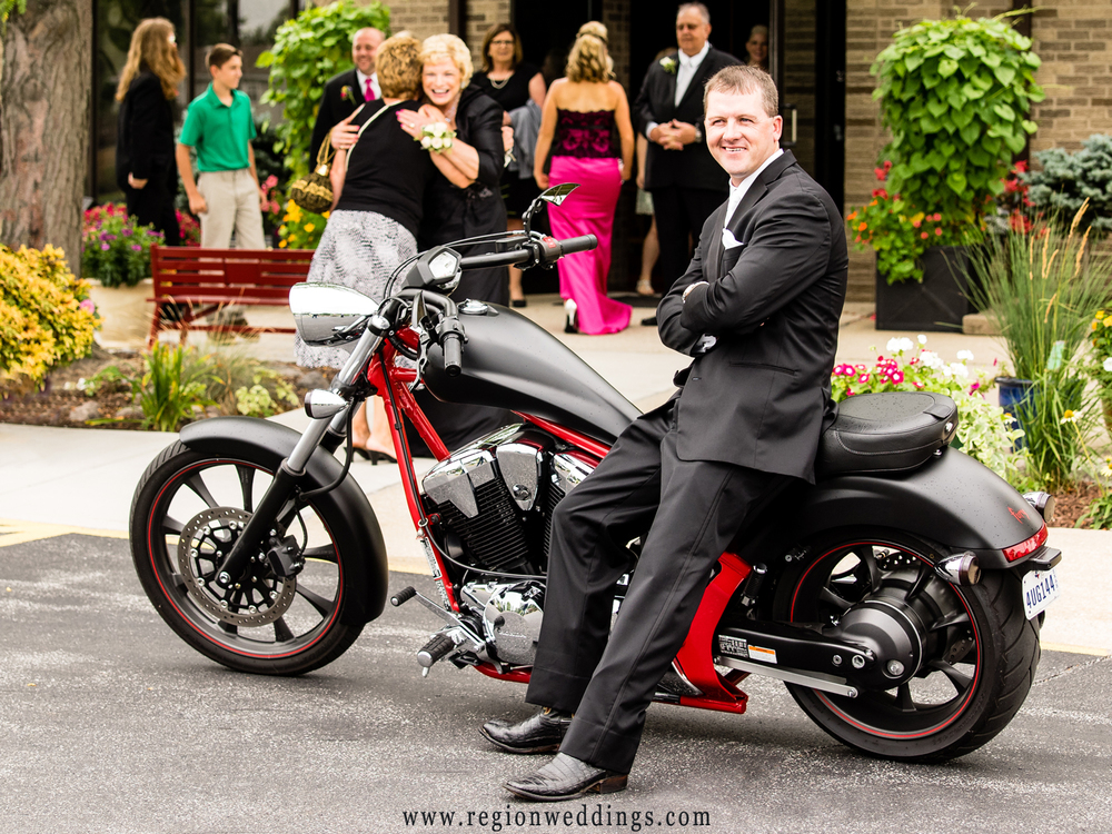 The groom arrives to his wedding at St. Maria Goretti via motorcycle and black tuxedo.