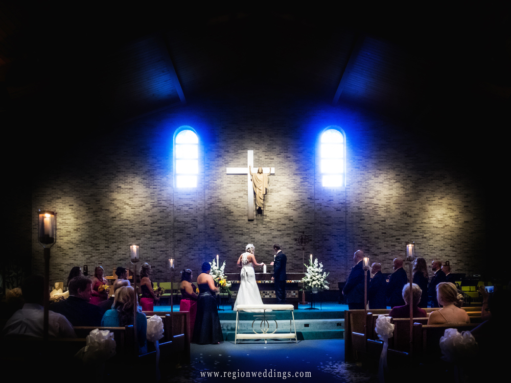 The bride and groom light unity candles at St. Maria Goretti Roman Catholic Church.