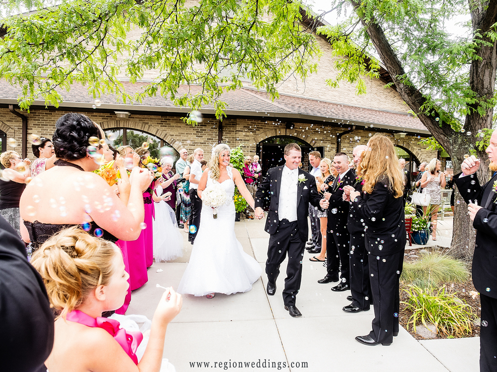 The bride and groom exit as bubbles surround them at St. Maria Goretti Church.