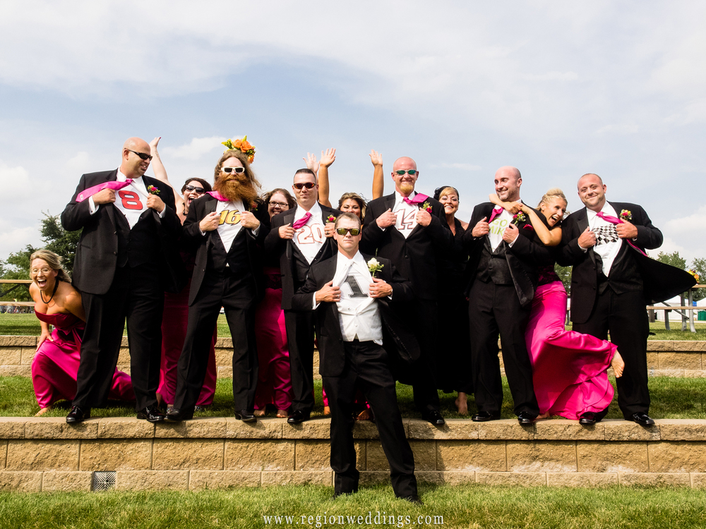 Bridesmaids photo bomb the groomsmen in this fun wedding photo.