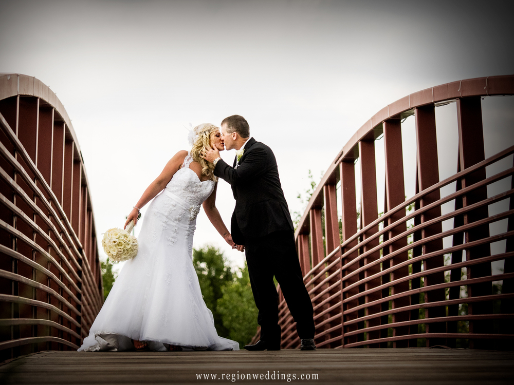 The bride and groom kiss atop the Centennial Park bridge in Munster, Indiana.