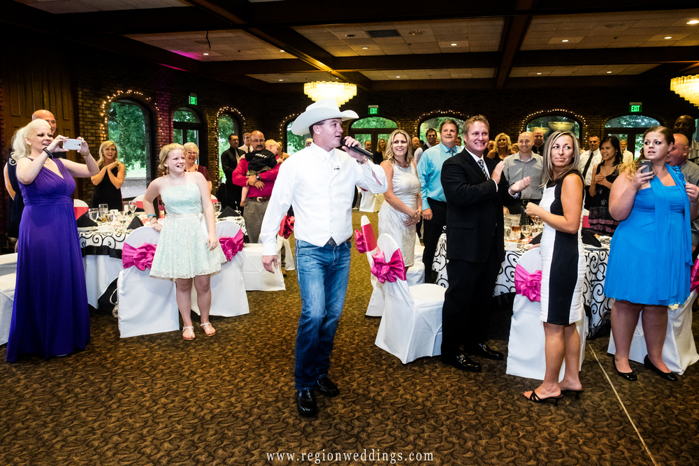 The groom enters his reception in a cowboy hat singing a country song.