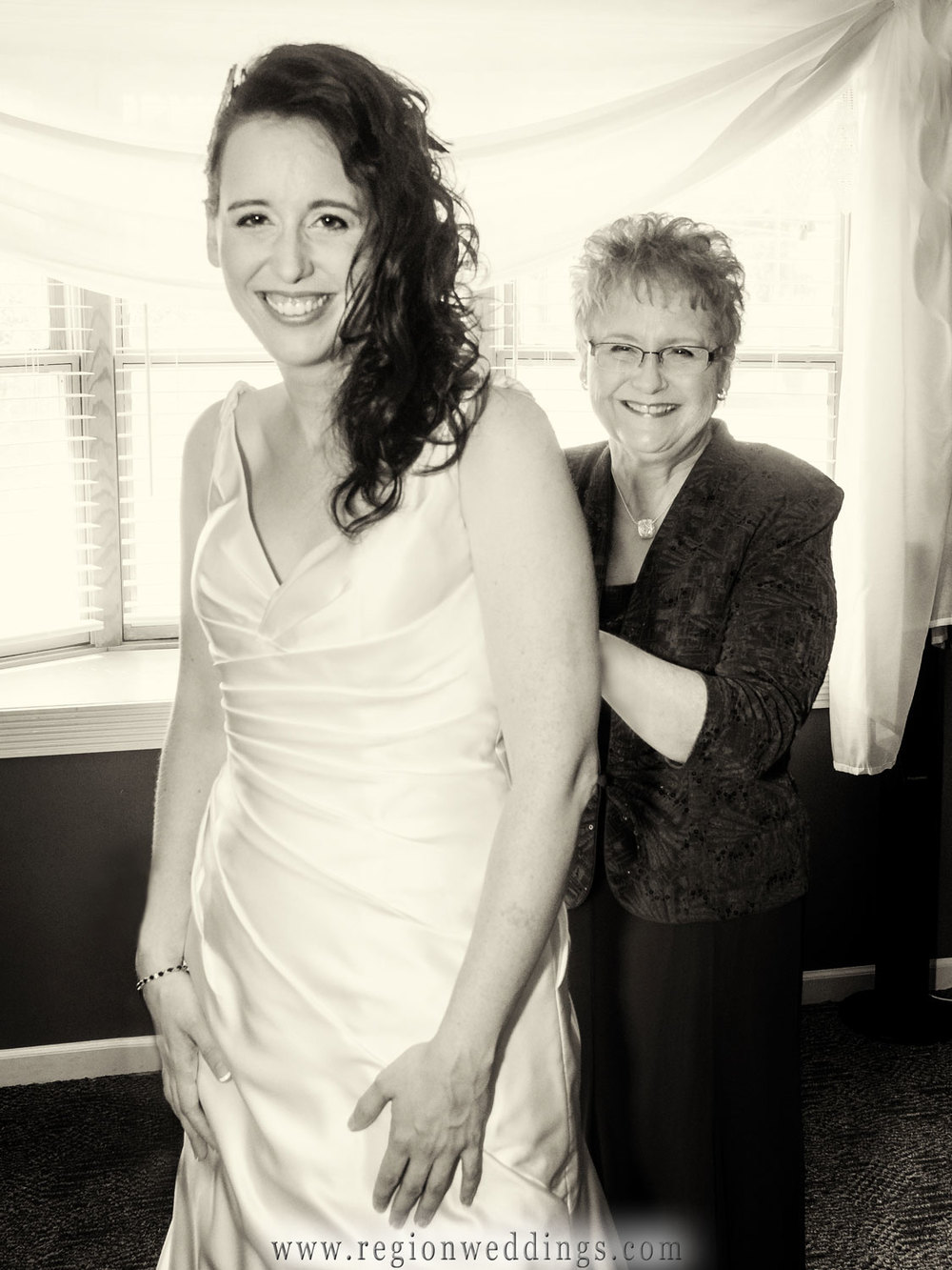 Mom zips up her daughter's wedding dress on wedding day.