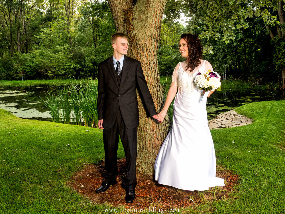 First look for the bride and groom besides a tree overlooking a pond in Griffith, Indiana.
