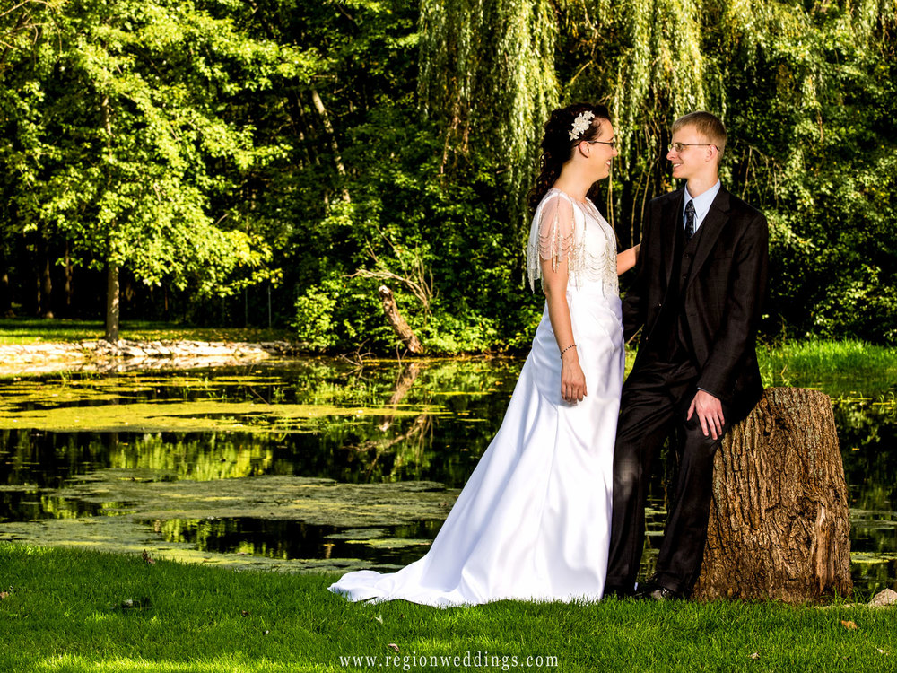 Beautiful greenery reflects into a small pond as the bride and groom gaze at each other.