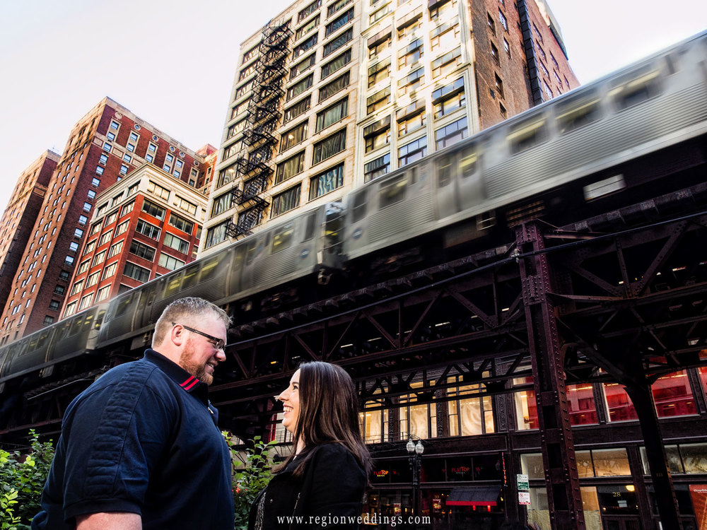 The L train speeds past an engaged couple in downtown Chicago.