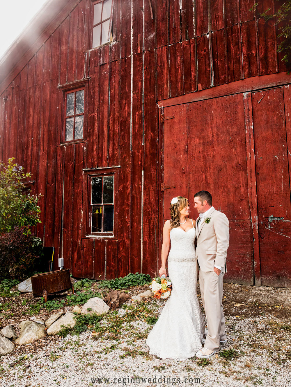 Sun rays illuminate the behind the red barn as the bride and groom gaze at each other.
