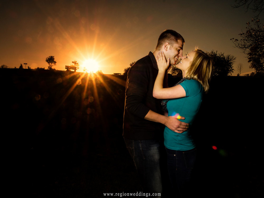 A sun burst star explodes in the sky in this Fall engagement photo.