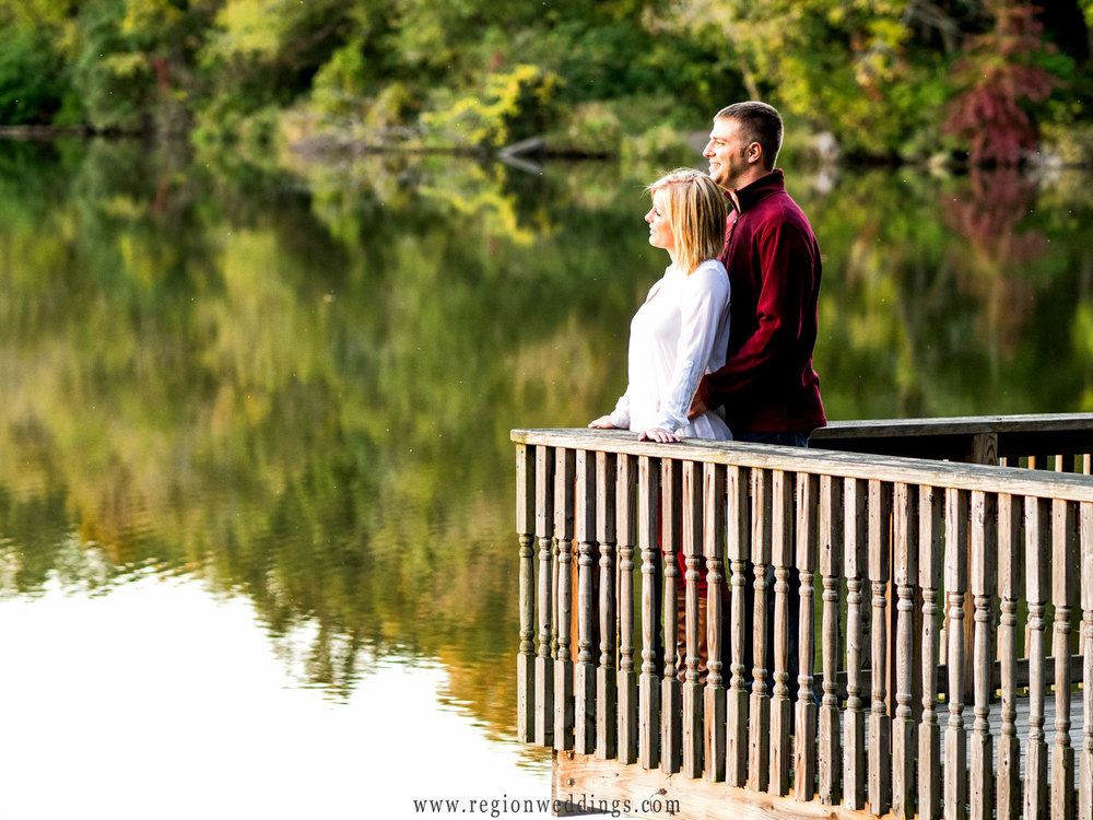 An engaged couple overlooks the serene lake from the edge of a pier.