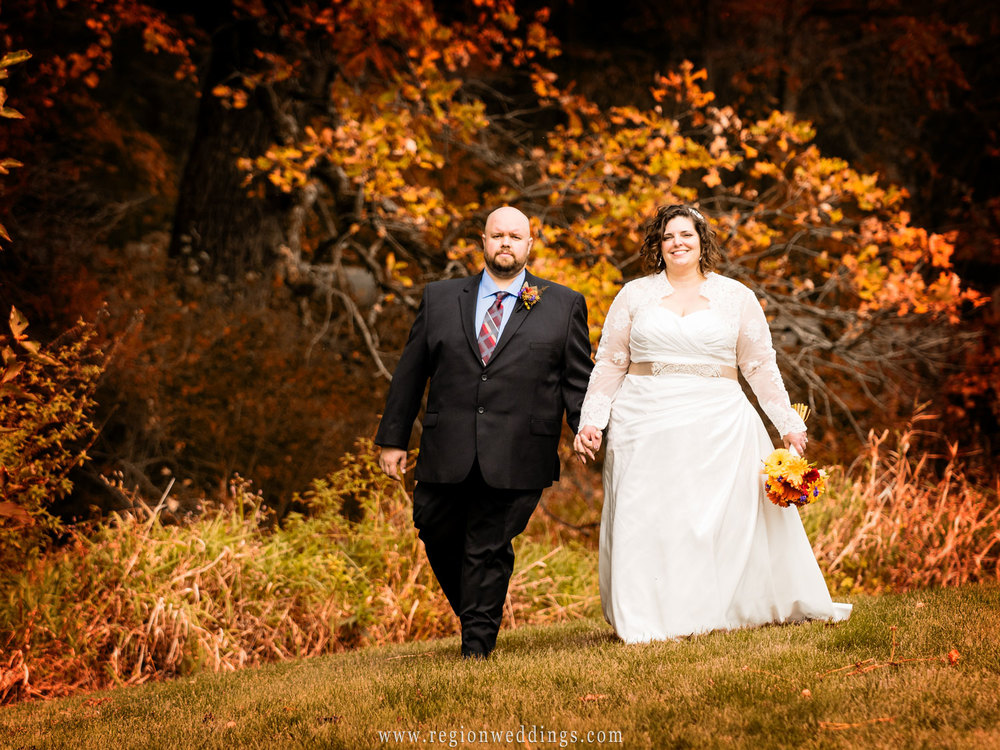 Fall colors come to life as the bride and groom take a walk at Taltree Arboretum in Valparaiso, Indiana.
