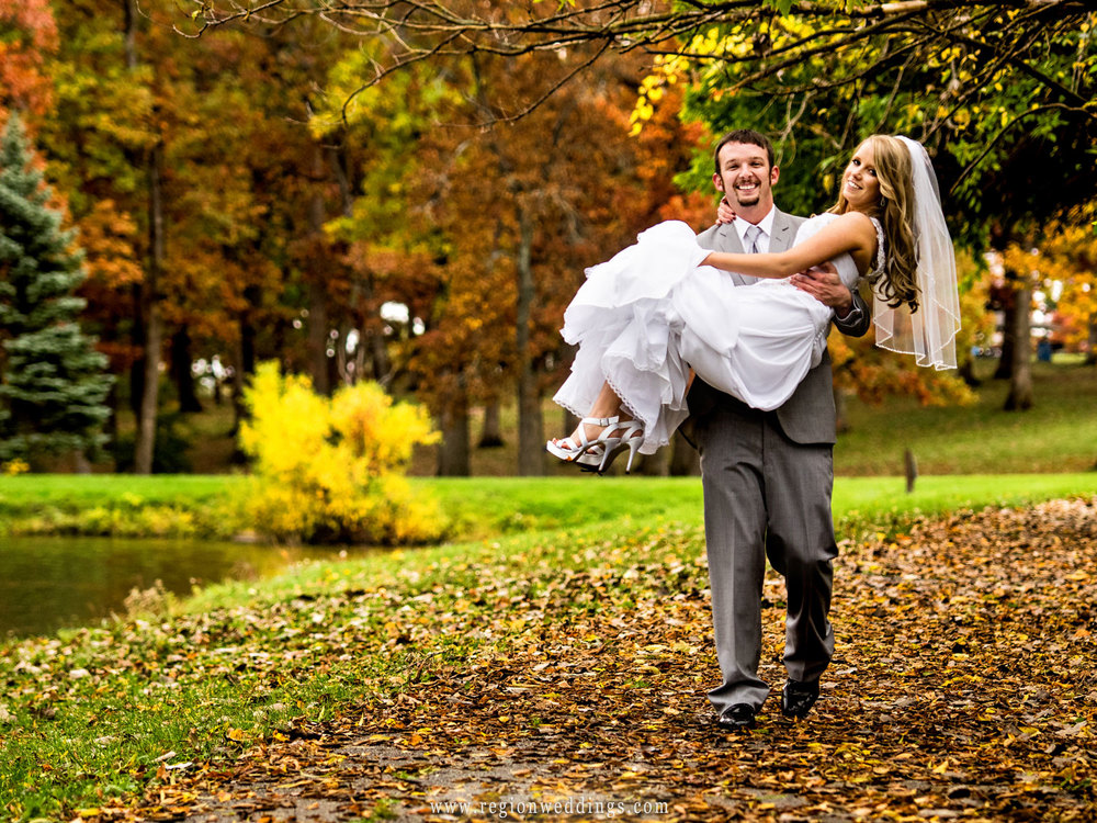 The groom carries his bride through leaves in Crown Point, Indiana.