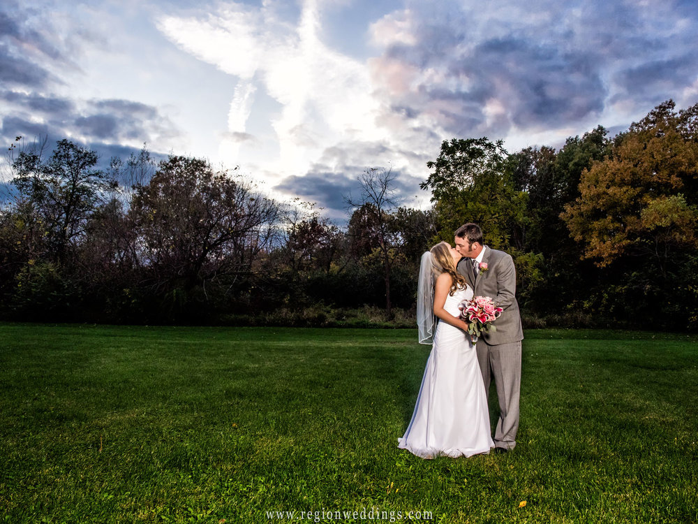 The newlyweds kiss as nightfall rolls in at the Halls of Saint George in Schererville, Indiana.
