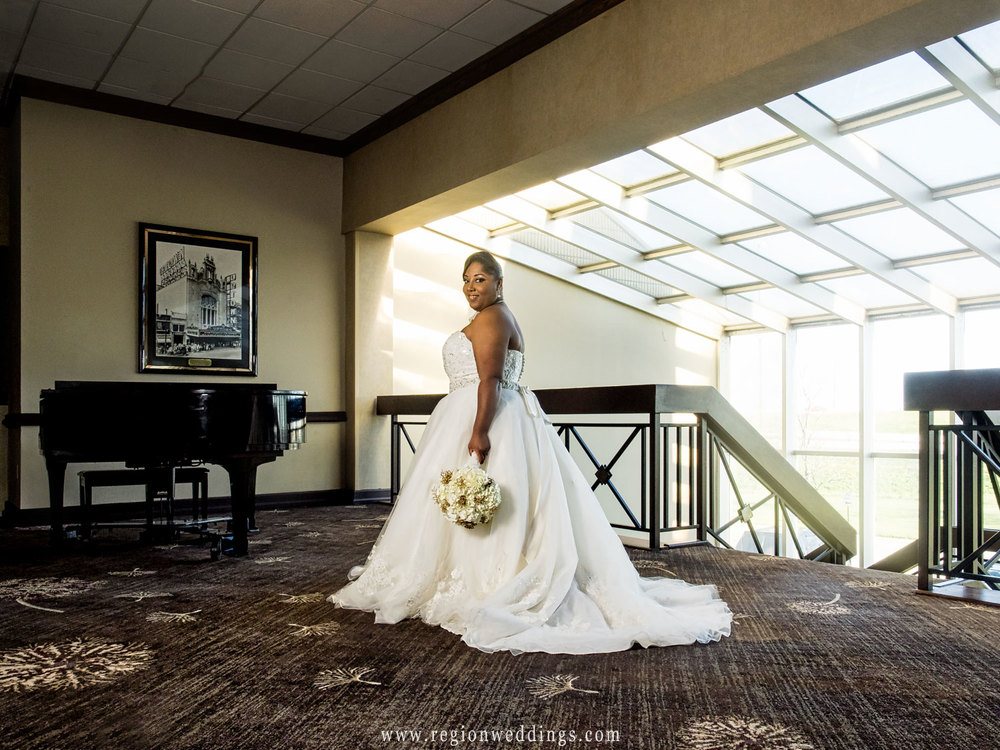 The bride shows off her dress next to the grand piano at Radisson Hotel.