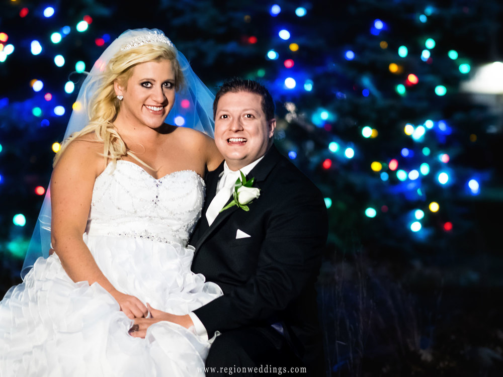 The bride and groom in front of the Crown Point Christmas tree on their wedding day.