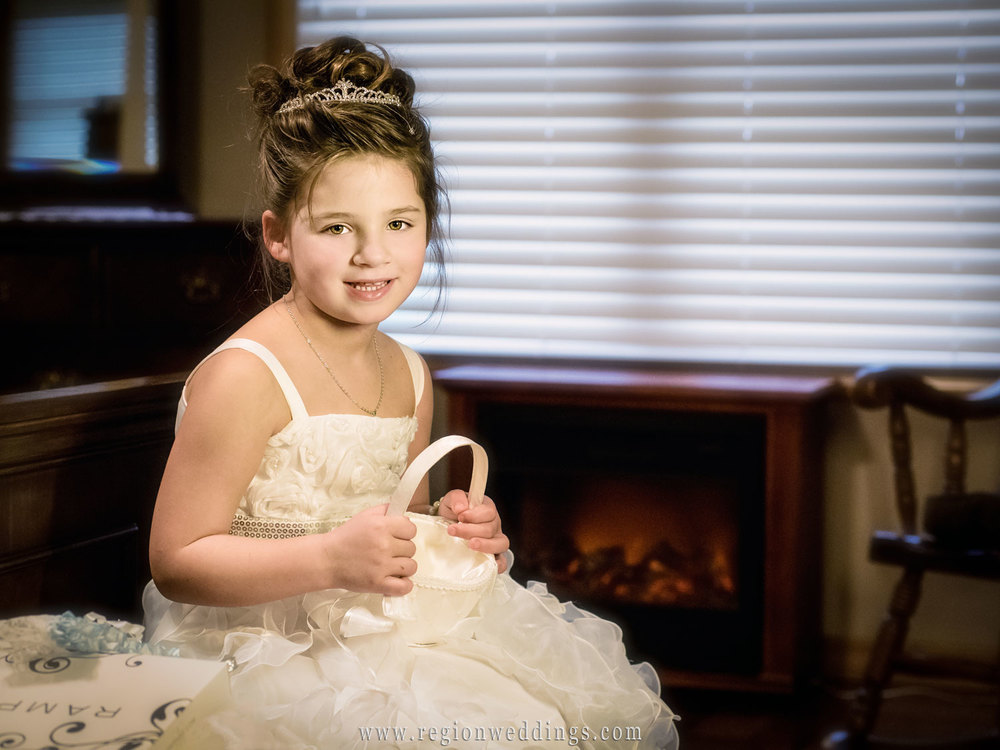 The flower girls sits by the fireplace in her dress on wedding day.
