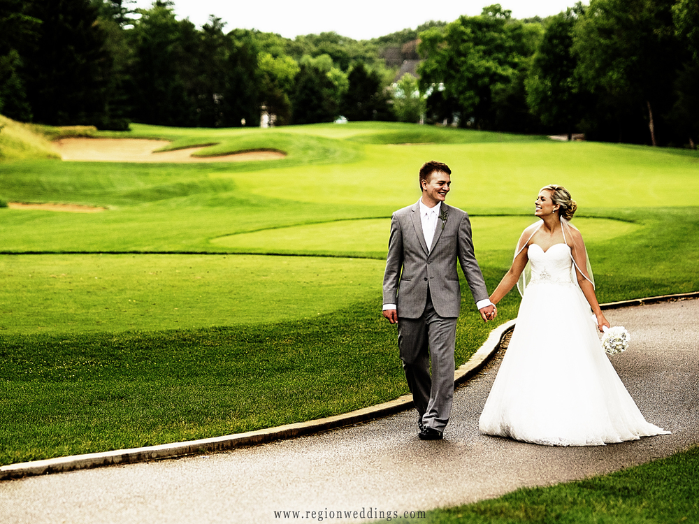 The bride and groom take a walk at Sandy Pines Pavilion in Demotte, Indiana.