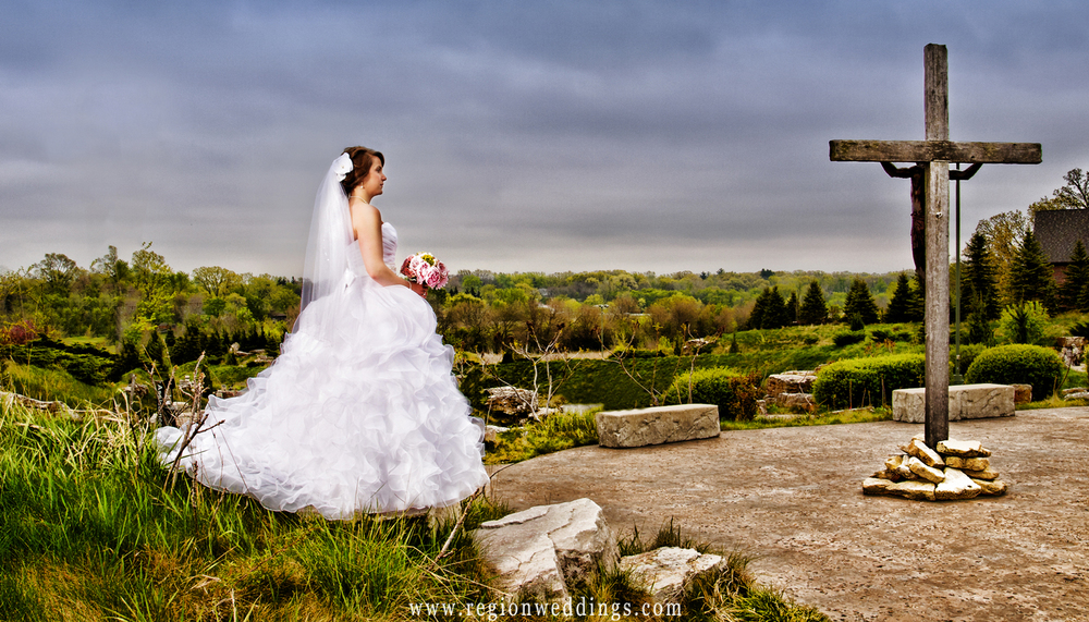 A bride faces the cross outside of Saint John the Evangelist Church in St. John, Indiana.