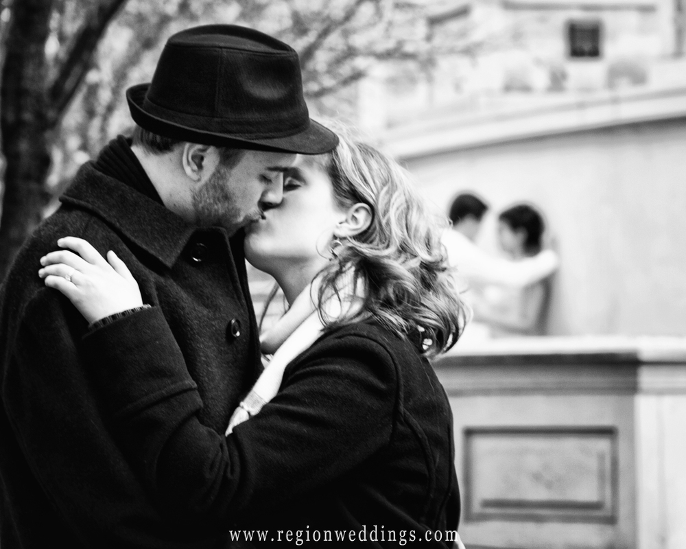 A couple kisses in the streets of Chicago in this black and white engagement photo.