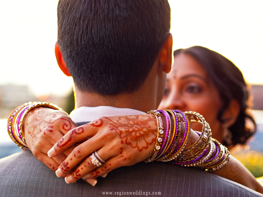 An Indian bride shows off her henna decorated hands as she embraces the groom.