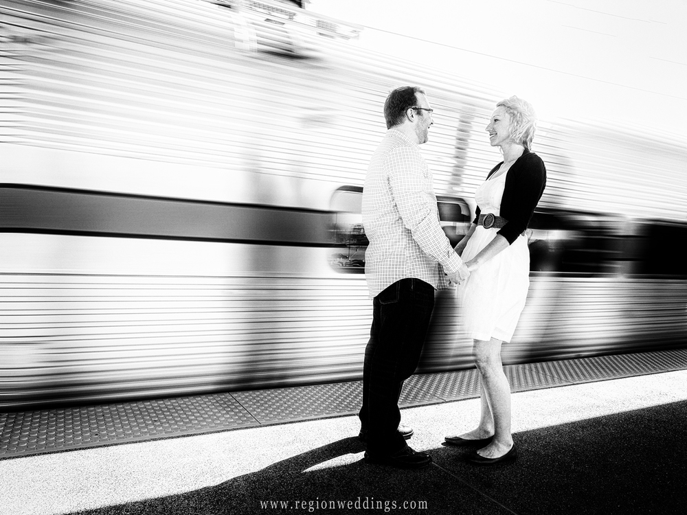 The train speeds by a couple on the train platform for their engagement photo.