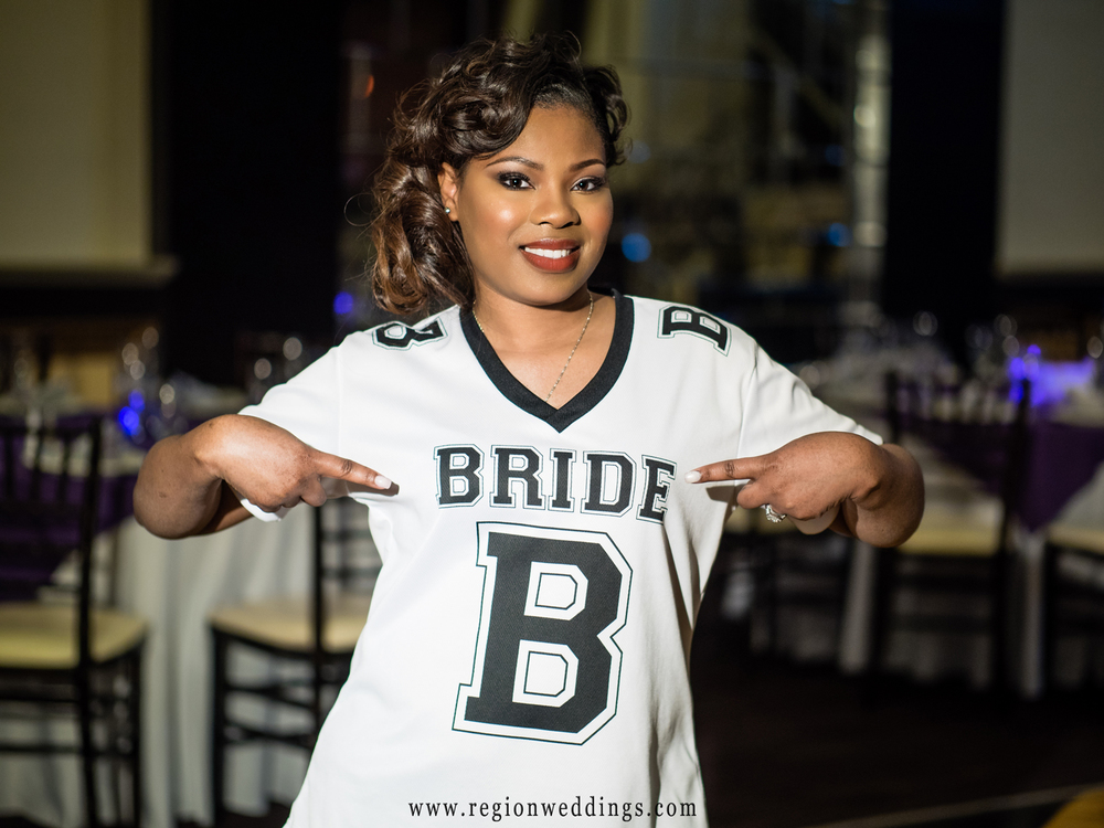 "The bride shows off her ""bride jersey"" inside The Allure ballroom."