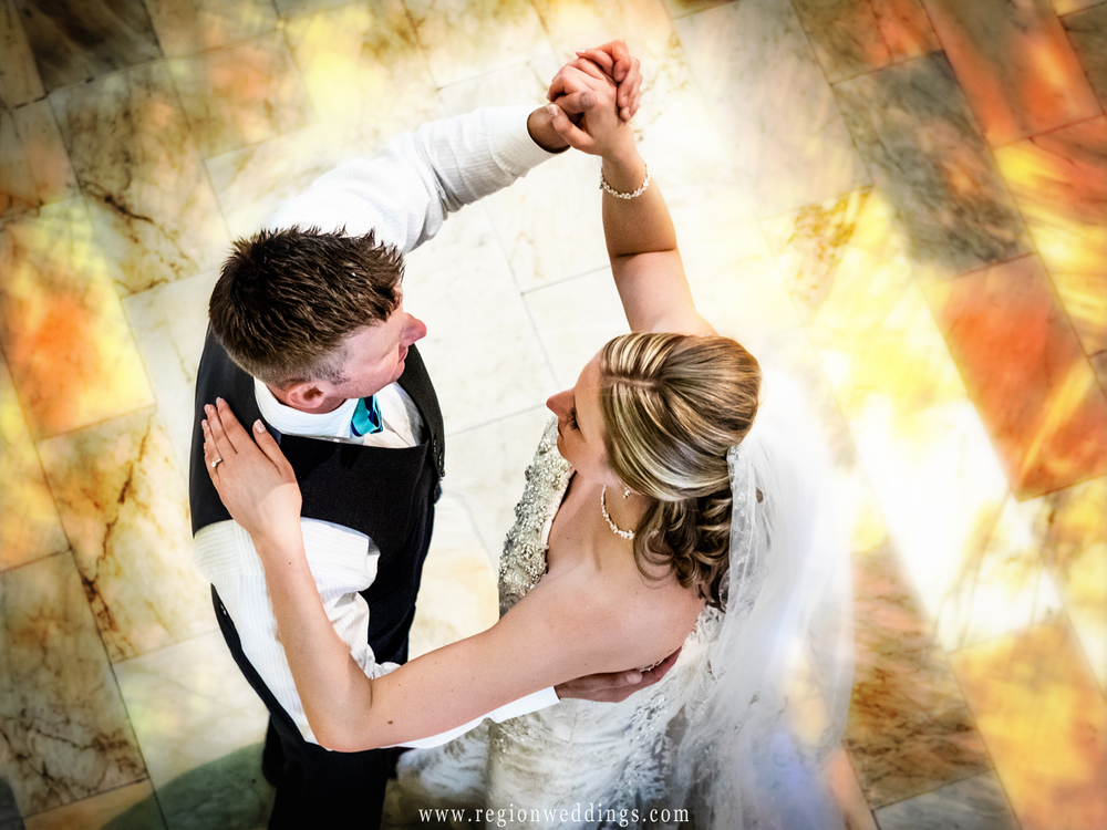 The bride and groom dance upon the marble floor.