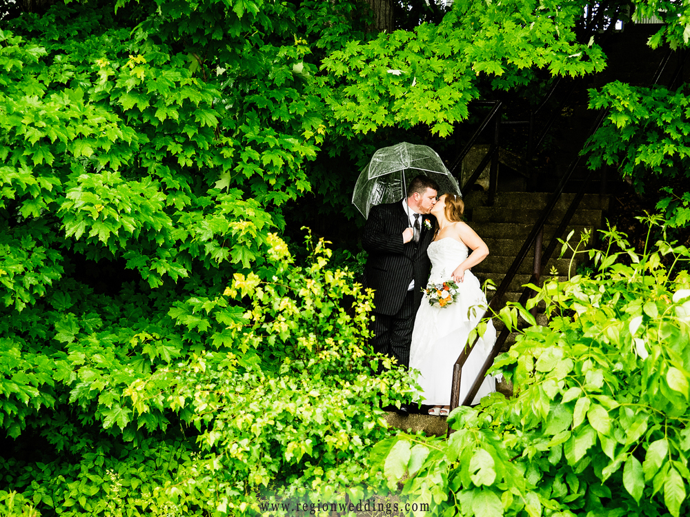 The bride and groom brave the rain for their wedding photos.