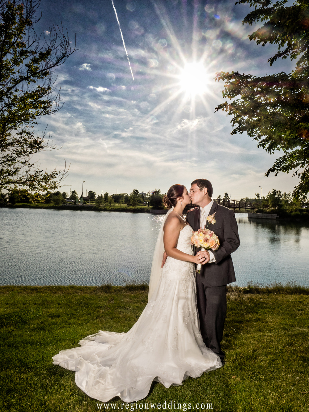 The bride and groom kiss underneath a sunburst after their outdoor summer wedding.