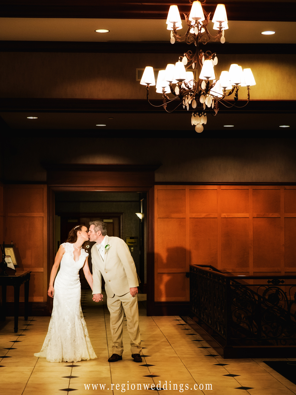 The bride and groom kiss romantically underneath a chandelier at Sand Creek Country Club.