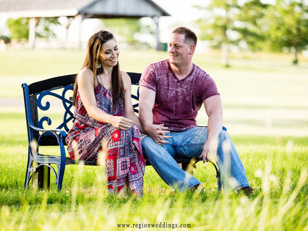 A couple talks and laughs on a bench for their engagement photos on a farm in Lowell.