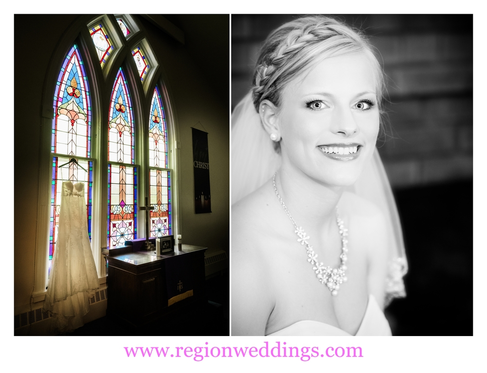 The bride's dress hangs in front of stained glass windows at the church.