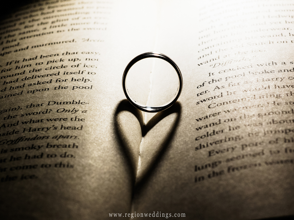 Shadow of a heart with a wedding ring placed inside a book.