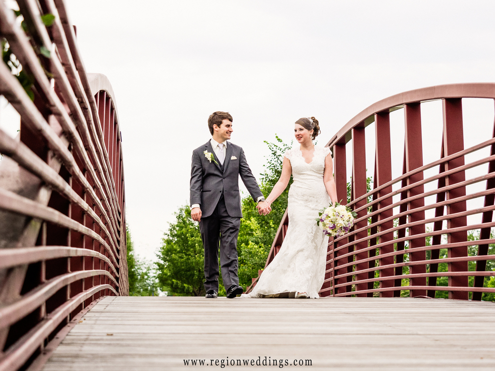 The bride and groom walk across the bridge at Centennial Park.