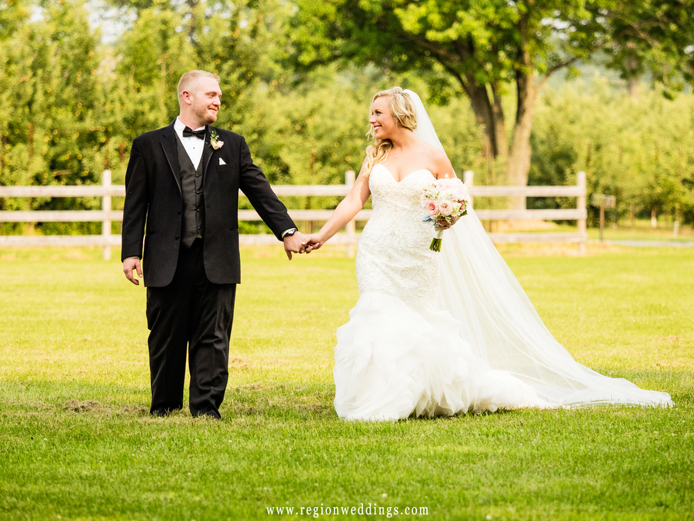 Bride and groom walk along the farmland of County Line Orchard.