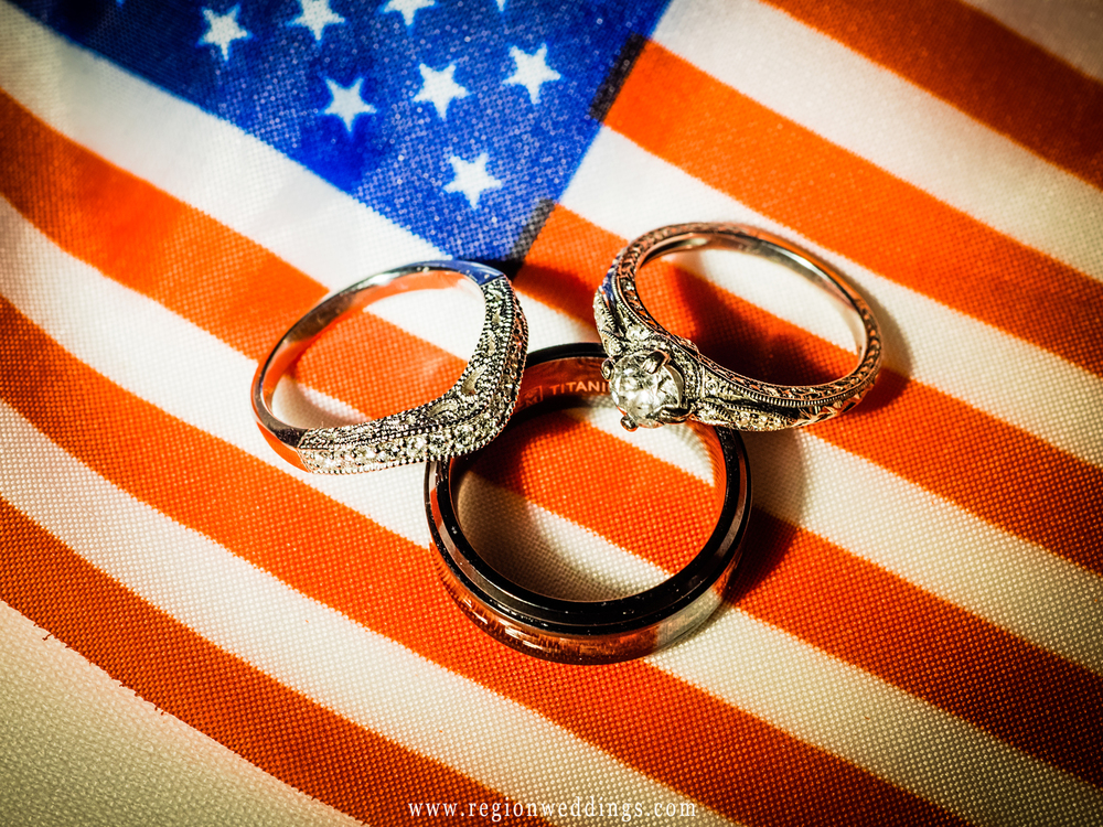 Wedding rings rest upon American flag stars and stripes.