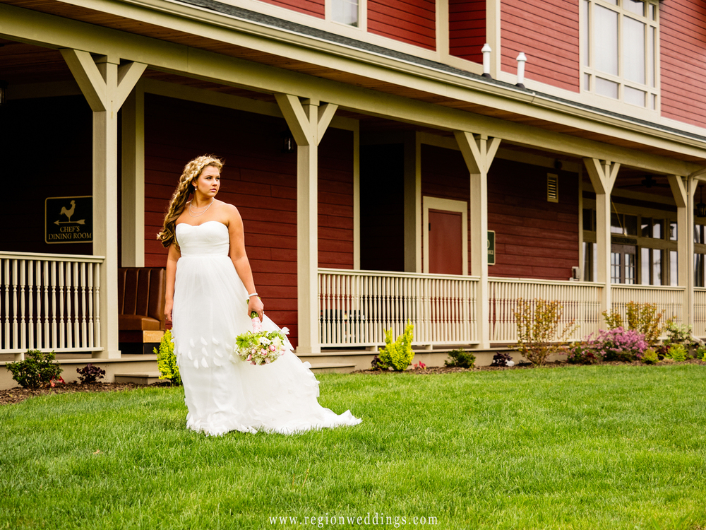 The bride walks alone with her dress trailing behind her.