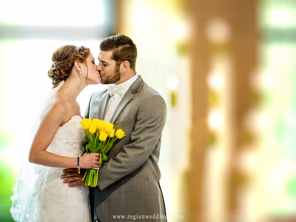 Bride and groom kiss at the altar of Christ Lutheran Church.