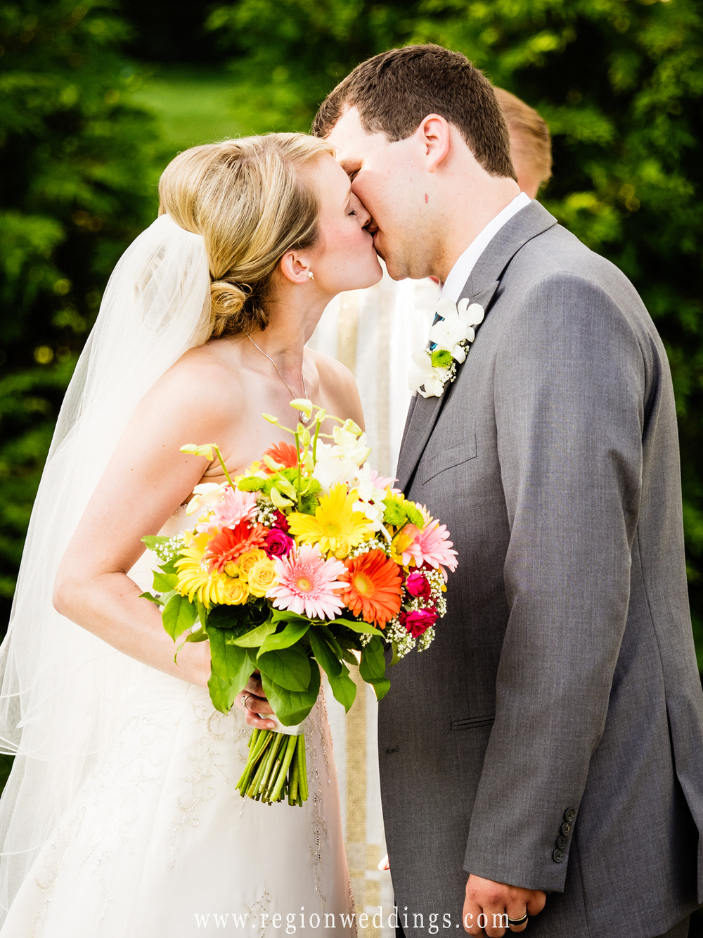 First kiss at an outdoor wedding ceremony.