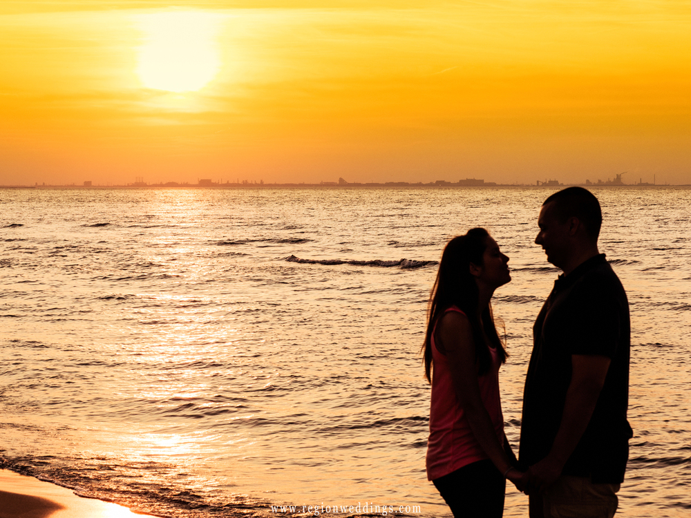 A sunset silouhette of a couple on a Lake Michigan beach.