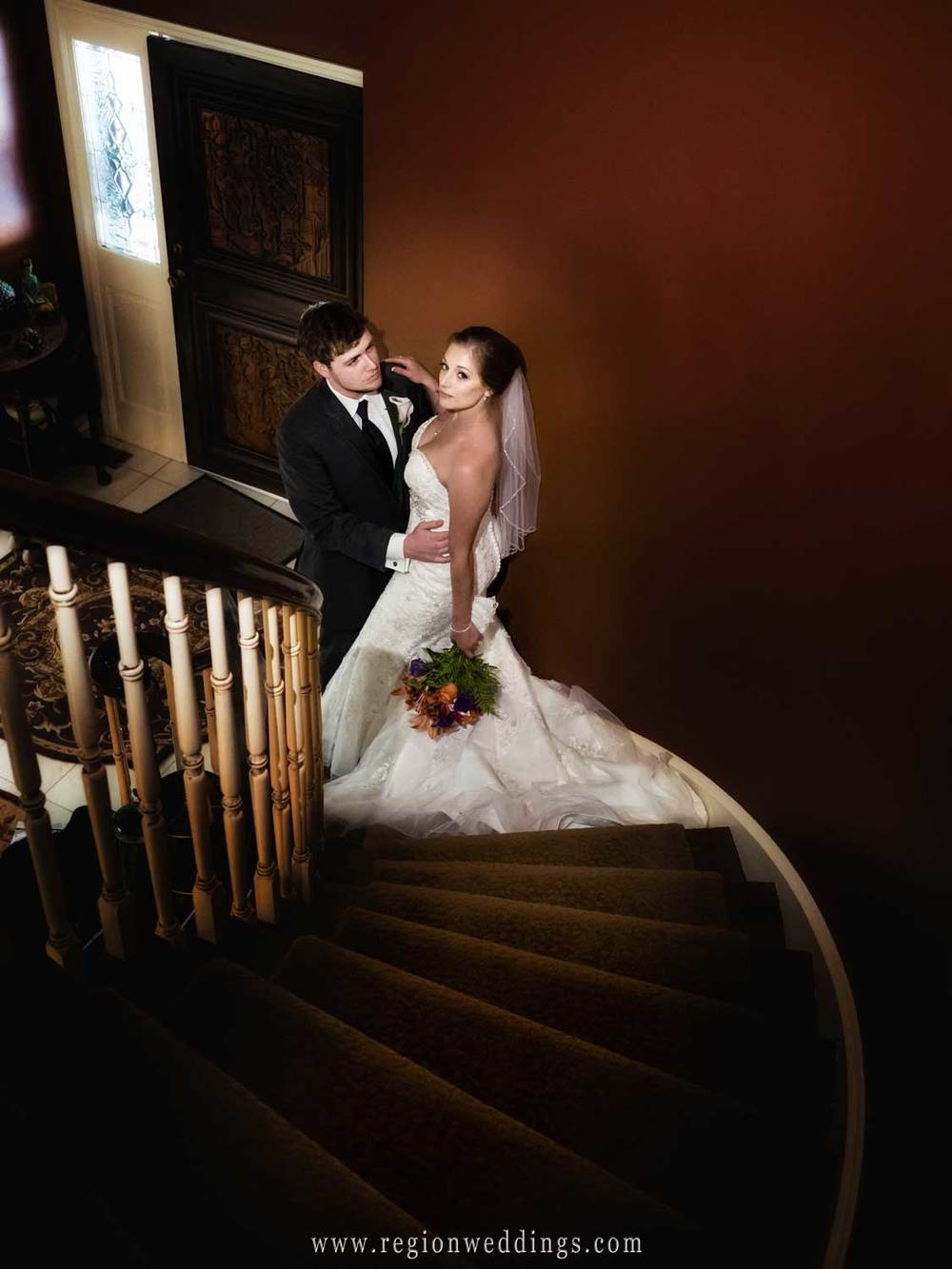 The bride and groom embrace at the bottom of a staircase.