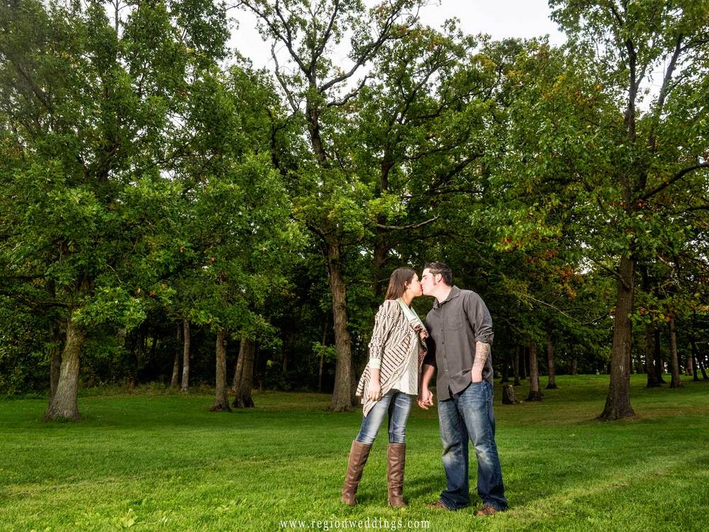A young couple kisses beneath the greenery of Lemon Lake Park for their engagement session.
