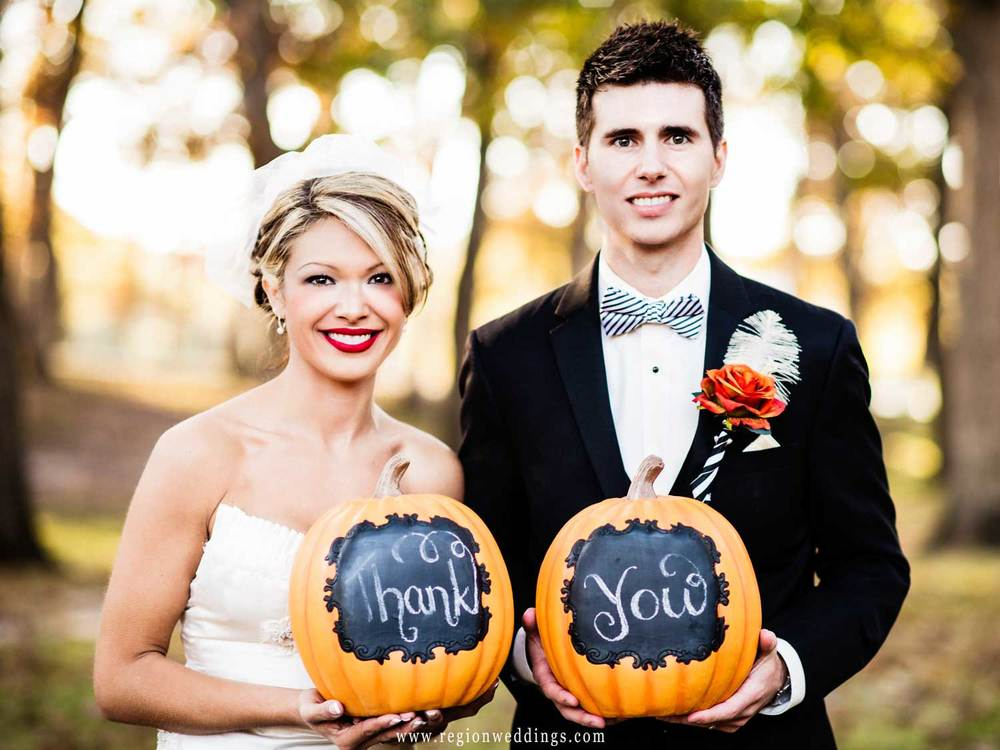 Bride and groom hold pumpkins engraved with Thank You.