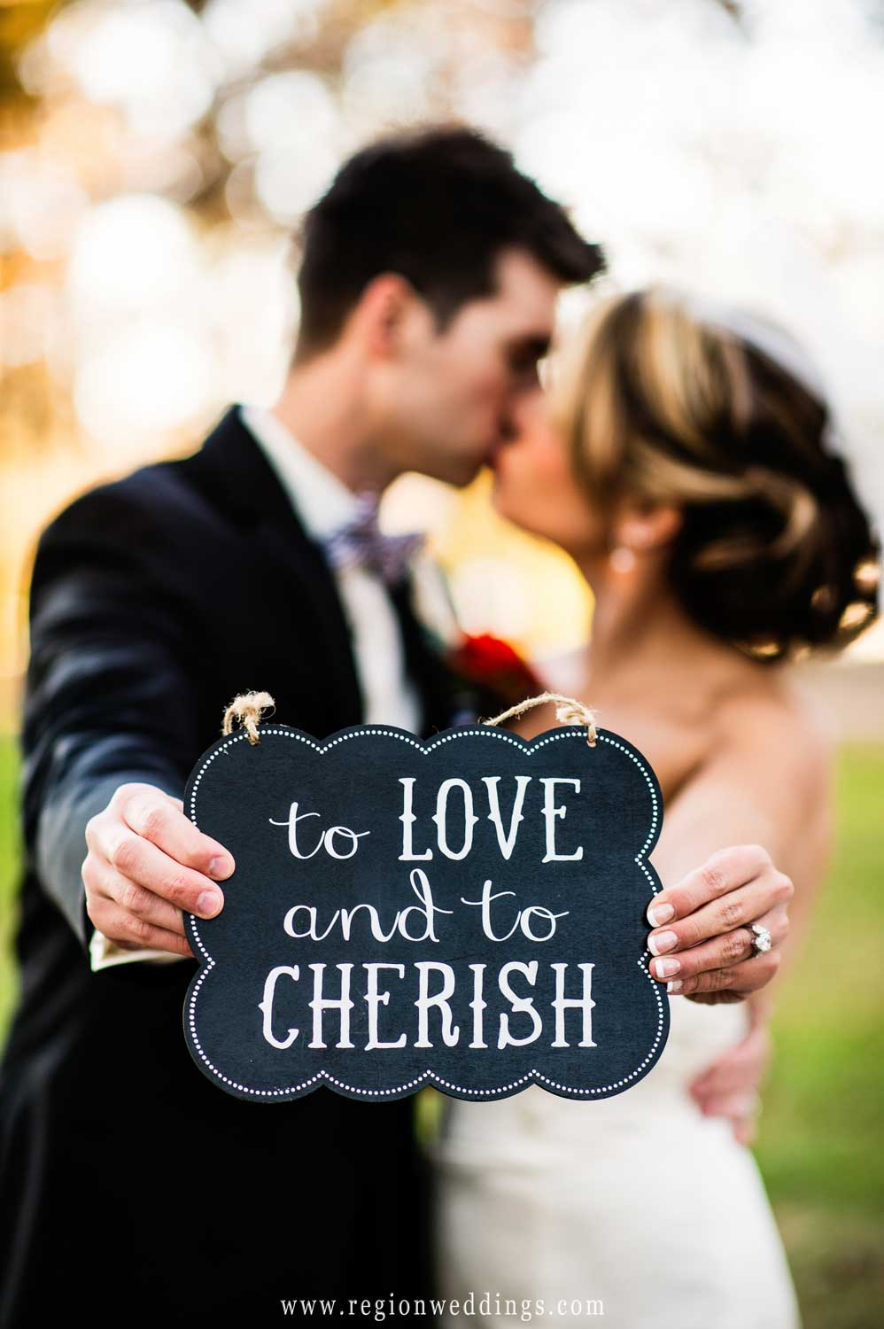 The bride and groom hold a sign that states To Love and To Cherish.