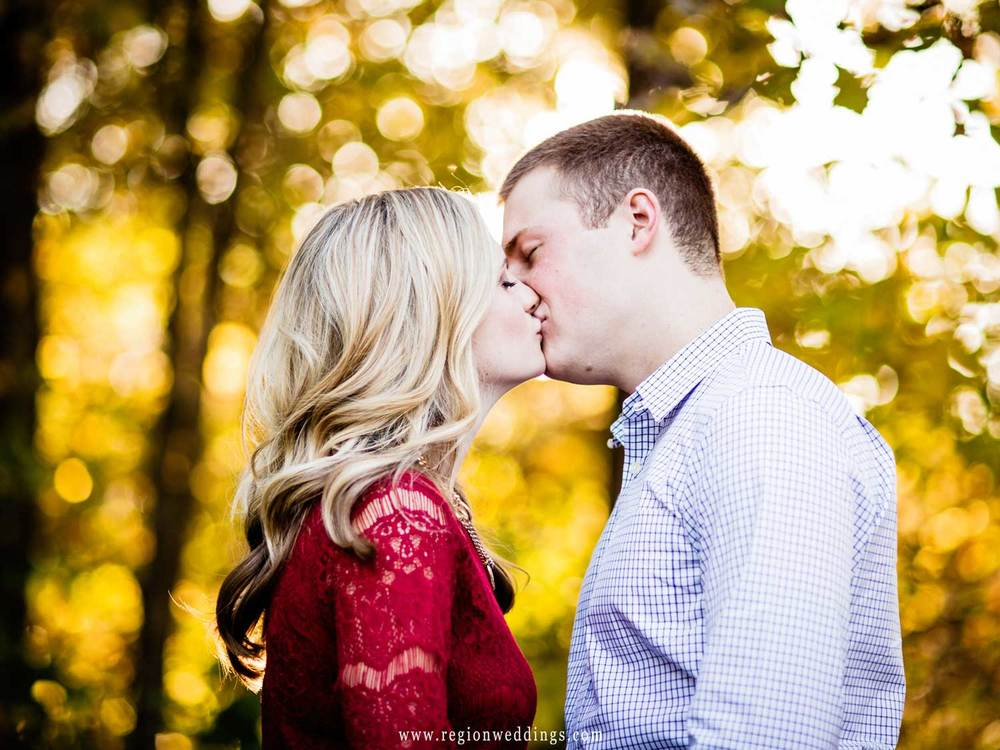 A back lit kiss in the woods.