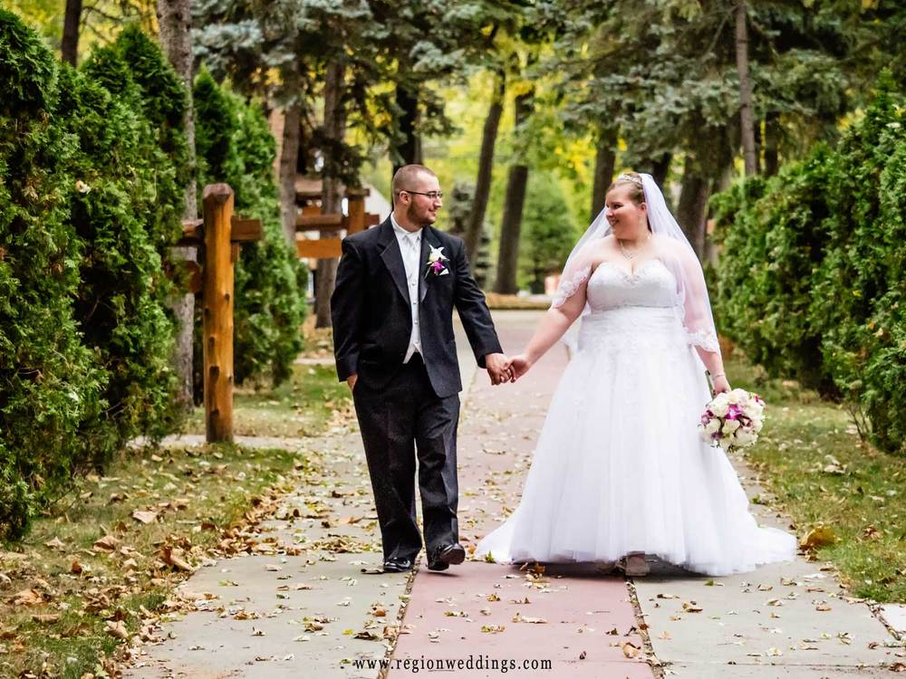 The bride and groom stroll through the walkways of Carmelite Shrine in Munster, Indiana.